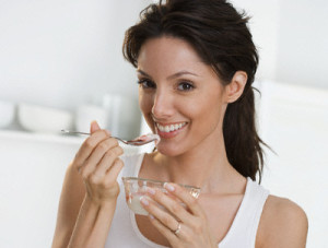 Smiling woman with dish of yogurt